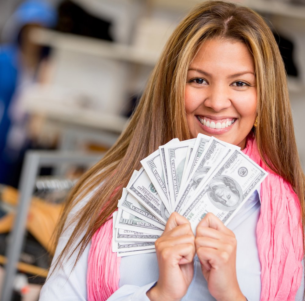 Rich shopping woman smiling and holding a bunch of money